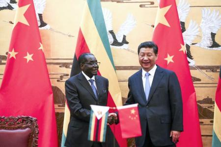 Zimbabwe's President Robert Mugabe (L) and his Chinese counterpart Xi Jinping shake hands during a signing ceremony at the Great Hall of the People in Beijing August 25, 2014. REUTERS/Diego Azubel/Pool