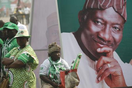 A woman sits beside an electoral poster of Nigeria's President Goodluck Jonathan during the flag-off for his campaign for a second term in office, in Lagos January 8, 2015. REUTERS/Akintunde Akinleye