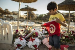 A boy holds a Tunisian flag as he stands near bouquets of flowers laid at the beachside of the Imperiale Marhabada hotel, which was attacked by a gunman in Sousse, Tunisia, June 27, 2015. REUTERS/Zohra Bensemra